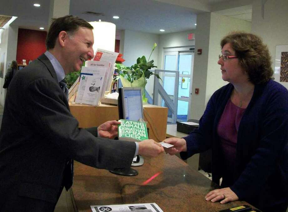 "First Selectman Kenneth Flatto, on left, checks out the first copy of ""Eating Animals"" at the Fairfield Public Library from library director Karen Ronald. The book is the latest ""One Book One Town"" selection. Photo: Genevieve Reilly / Fairfield Citizen"