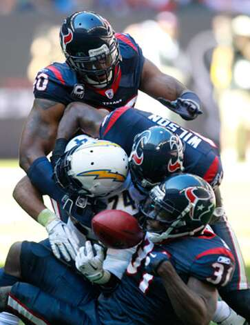 The Texans' Mario Williams (from top), Eugene Wilson and Bernard Pollard hit the Chargers' Ryan Mathews.