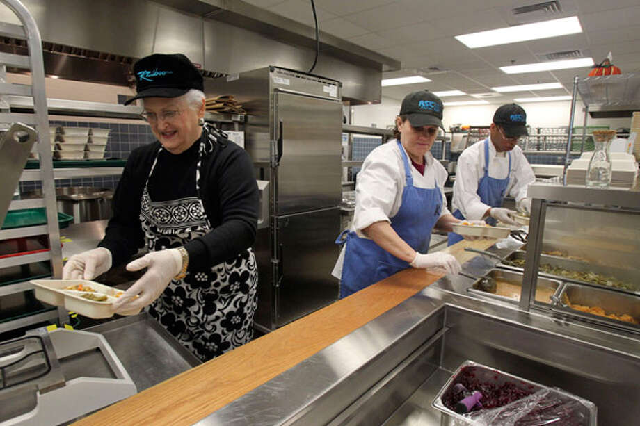 Noelie Bockholt (from left), Brenda Ivy and Jimmie Davis prepare meals for the Meals on Wheels program that operates out of the new Kronkosky Place in Boerne.