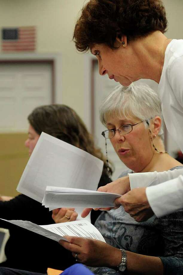 Denise Weeks, back, and Melinda Valencia look at recount results during the ballot recount at City Hall Annex on Wednesday, November 1, 2010. Photo: Lindsay Niegelberg / Connecticut Post