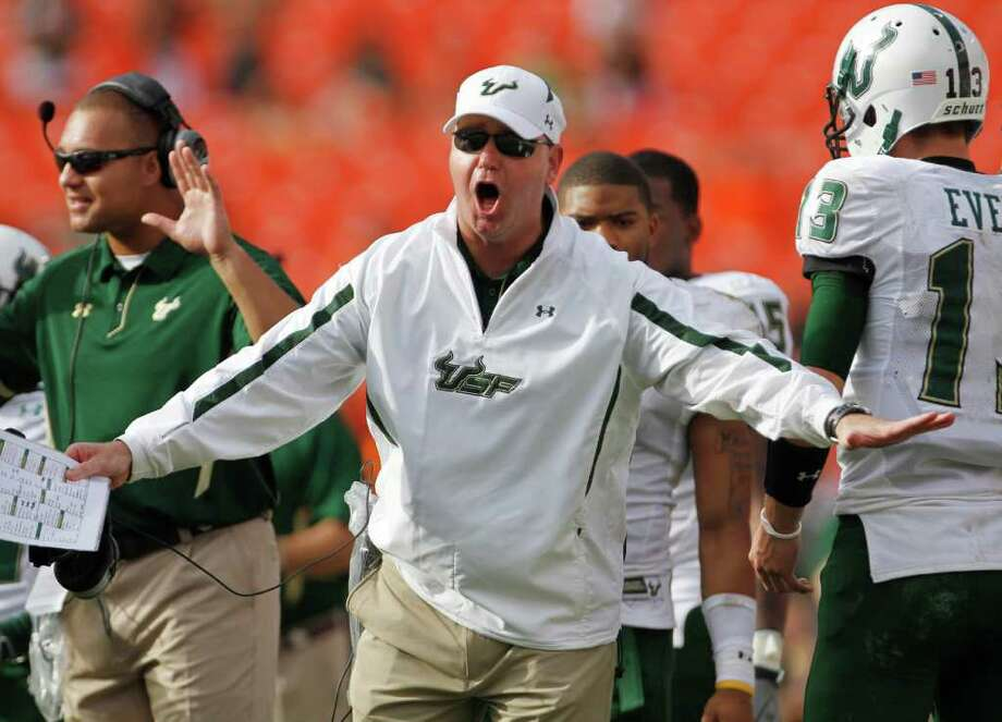 South Florida coach Skip Holtz, center, protests a penalty call during the second half of an NCAA college football game against Miami, Saturday, Nov. 27, 2010, in Miami. South Florida won 23-20 in overtime. (AP Photo/J Pat Carter) Photo: AP