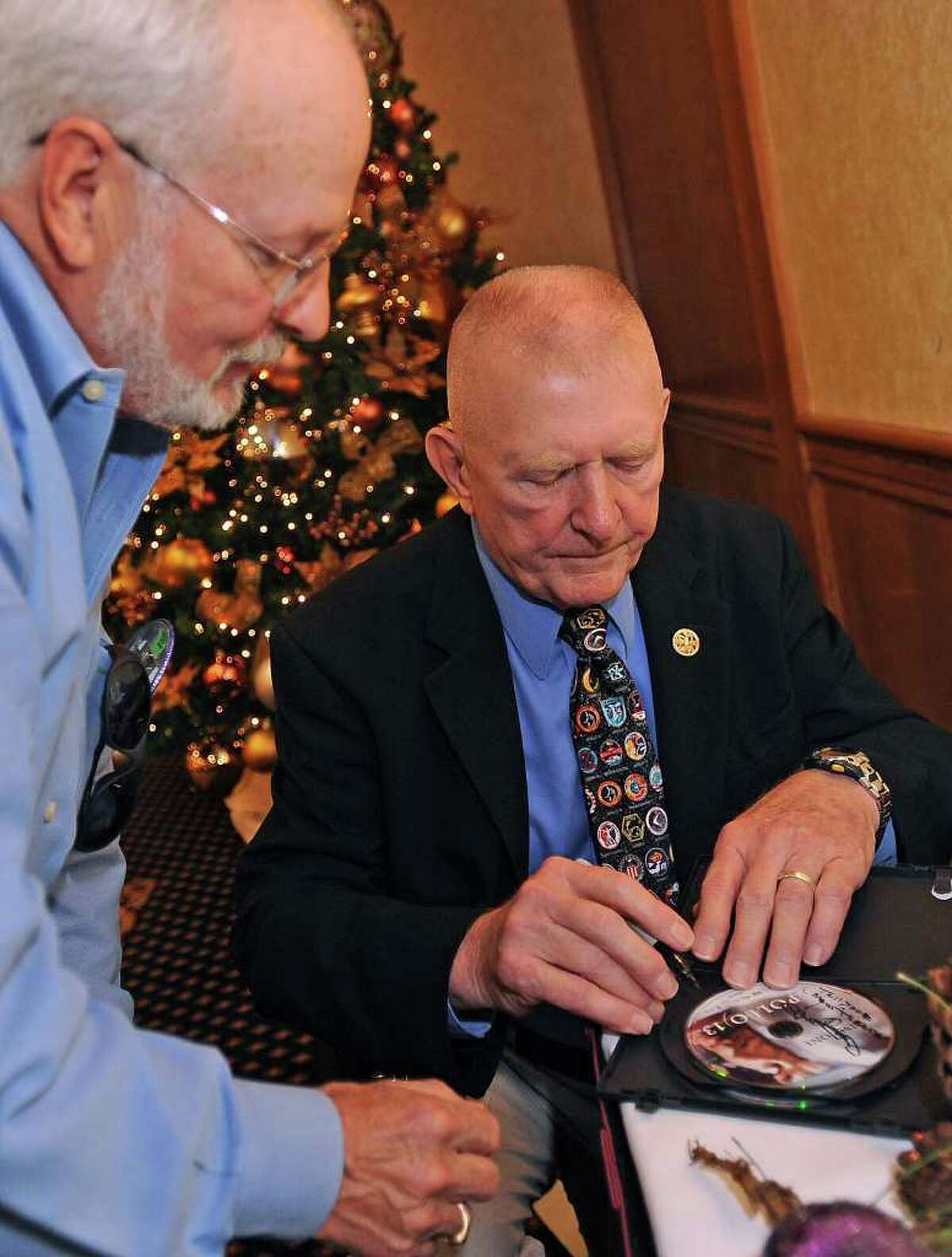 Gene Kranz former NASA mission director signs a copy of Apollo 13 for Ed Edson after the famed mission controller addressed the Beaumont Rotary Club on Wednesday. Guiseppe Barranco/The Enterprise