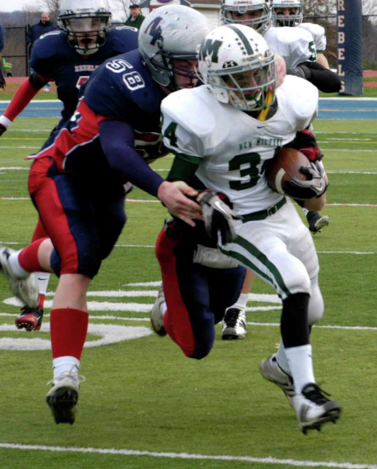 SPECTRUM/Tevon Leonard (34) drags a New Fairfield High tackler along for an extra yard or two for New Milford High School football during the Thanksgiving Day game called the Candlewood Cup at New Fairfield. Nov. 25, 2010