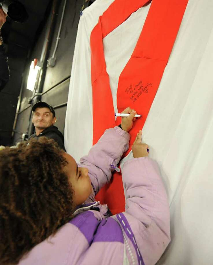 Sabina Monroe, age 7 of Schenectady, writes a message Wednesday on a red ribbon at an AIDS awareness event put on by the The Schenectady Damien Center at the Proctors Arcade in Schenectady. The Damien Center is trying to raise awareness about HIV/AIDS in the community. (Lori Van Buren / Times Union) Photo: Lori Van Buren