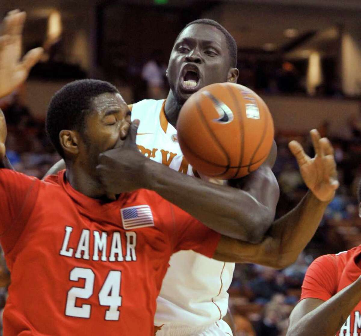 Texas forward Alexis Wangmene, rear, comes into close contact with Lamar forward Vincenzo Nelson while fighting for a loose ball during the first half of an NCAA college basketball game in Austin, Texas, Wednesday, Dec. 1, 2010. (AP Photo/Michael Thomas)