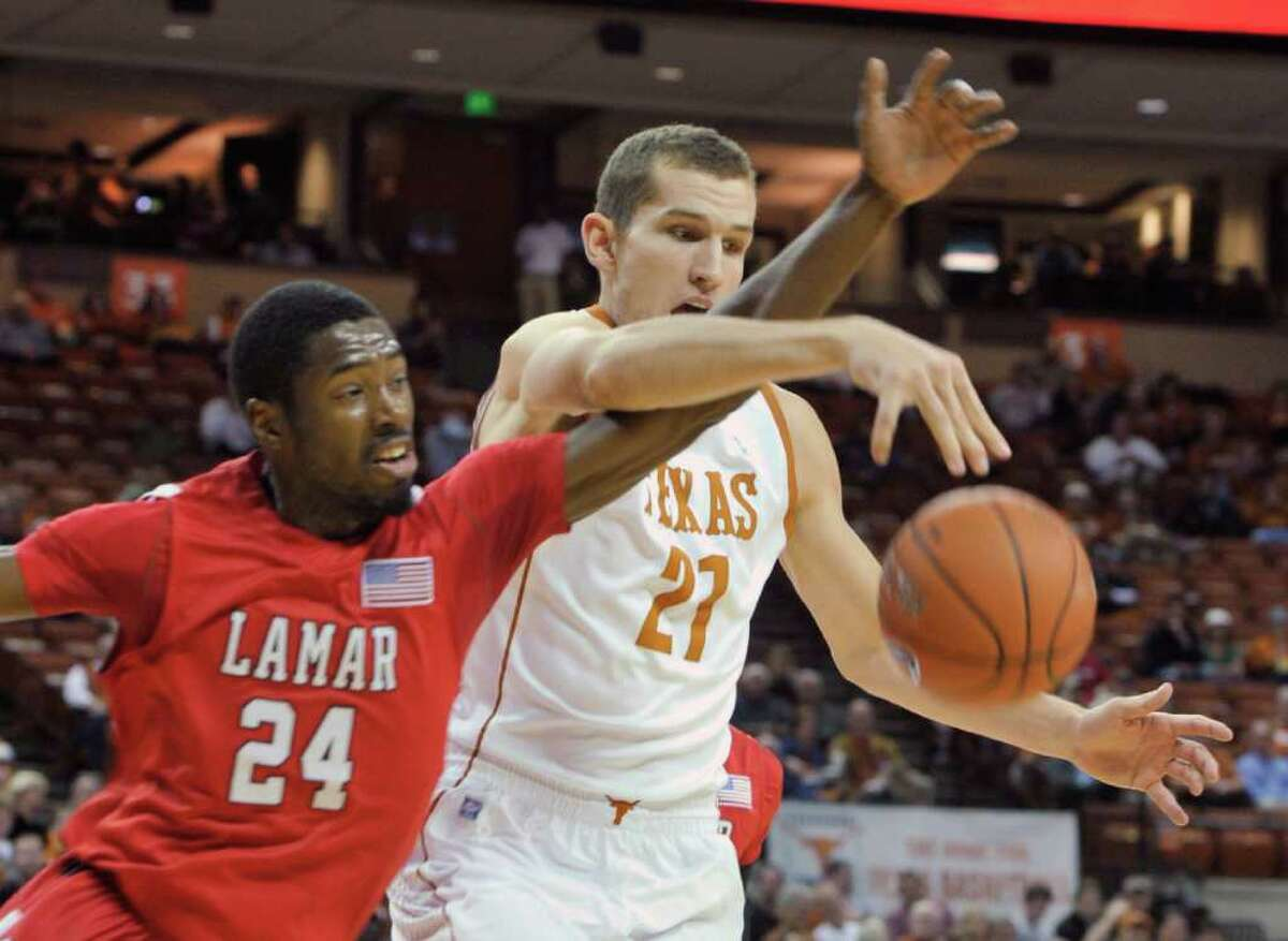 Texas forward Matt Hill, right, reaches for a rebound with Lamar forward Vincenzo Nelson during the first half of an NCAA college basketball game in Austin, Texas, Wednesday, Dec. 1, 2010. (AP Photo/Michael Thomas)
