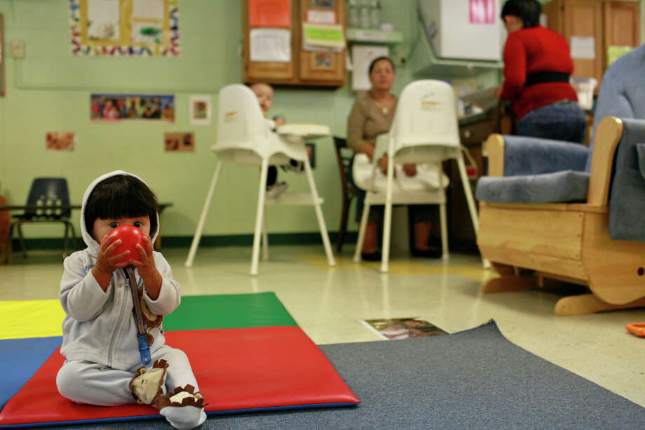 Eight-month-old David entertains himself as his mother, Samantha Saiz (far right), 17, drops him off at Healy-Murphy's day care before heading across the street to the center's high school, an alternative school for youths in crisis that emphasizes individualized education. Photo: LISA KRANTZ/lkrantz@express-news.net / SAN ANTONIO EXPRESS-NEWS