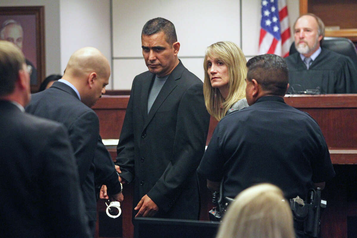 With defense attorneys Roland Garcia (left) and Carolyn Wentland bracketing their client, handcuffs are placed on former SAPD officer David Seaton after his sentence was read.