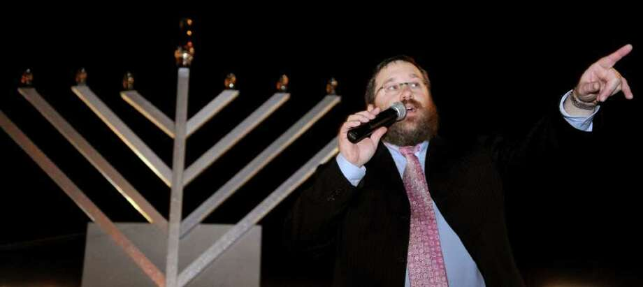 Rabbi Levi Stone directs visitors to the latkes during a menorah lighting ceremony in Westport on the first night of Hanukkah on November 1, 2010. Photo: Lindsay Niegelberg / Connecticut Post