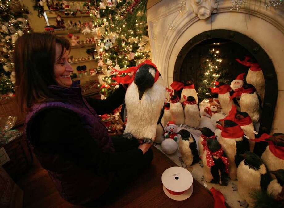 Stacey Weiss of Fairfield fashions individual scarves out of red ribbon for a flock of penguins in preparation for the 29th annual Fairfield Christmas Tree Festival at the Burr Homestead. Photo: Brian A. Pounds / Connecticut Post