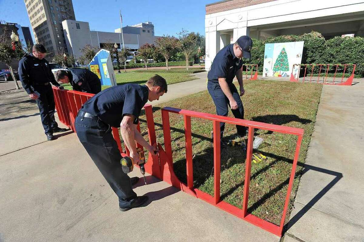 Beaumont firefighters install Christmas decorations at the Museum of Southeast Texas on Wednesday. Guiseppe Barranco/The Enterprise