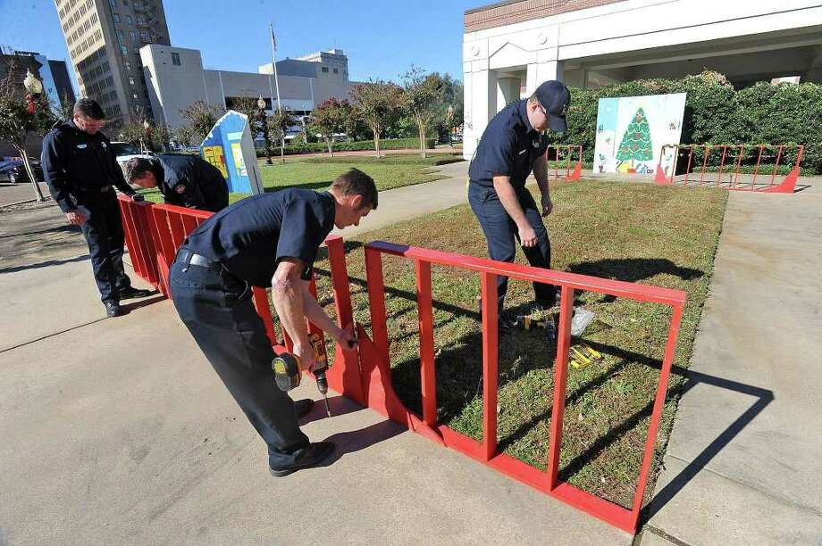 Beaumont firefighters install Christmas decorations at the Museum of Southeast Texas on Wednesday.  Guiseppe Barranco/The Enterprise / Beaumont