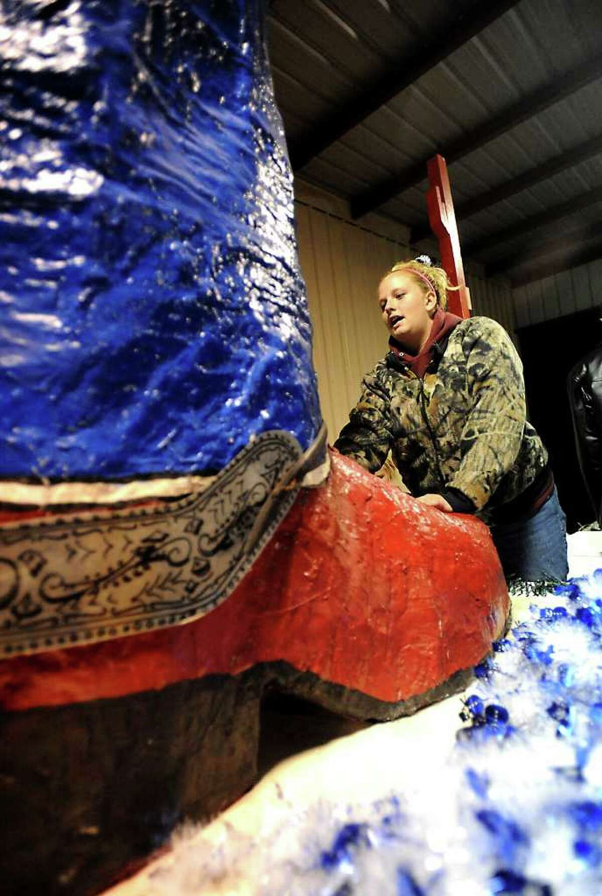 Camrie Helm of the LEO Junior Lion Club helps set up the Lion Club Christmas Parade Float in Orange. The parade begins at 6:30 p.m. Friday. Tammy McKinley/The Enterprise