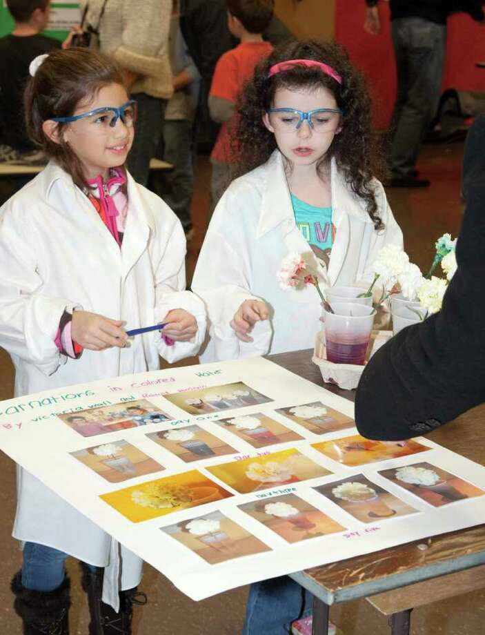 Victoria Wall and Rebecca Weinstein explain the results of their experiment at the recent Jennings School Science Expo. Photo: Contributed Photo / Fairfield Citizen contributed