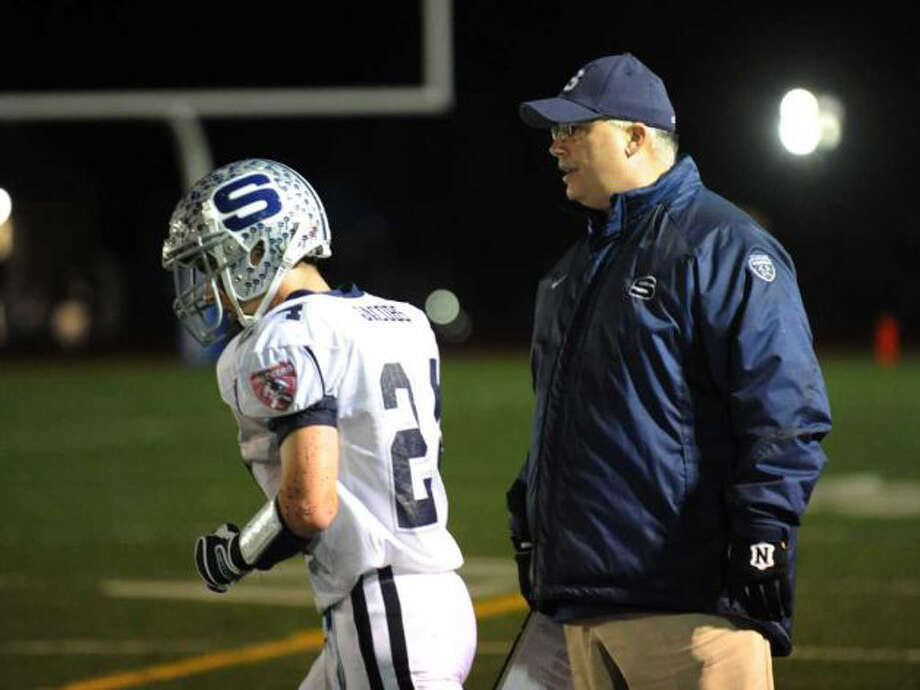 Staples senior Tyler Jacobs confers with Marce Petroccio before attemping the two-point conversion on Tuesday in the Class LL playoff game against Glastonbury. Jacobs was stopped short of the goal line and denied the two points in a 7-6 loss to the Tomahawks. Photo: Christian Abraham / Staff Photographer