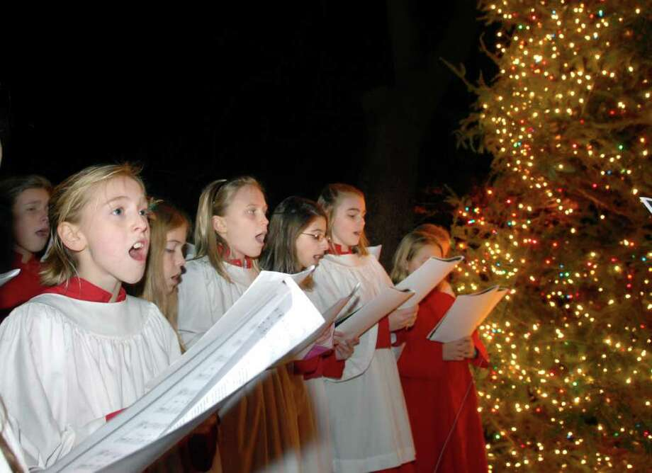 "Susie Moore, 12, left, along with other members of the St. Cecelia Choir of Girls, sing ""Silent Night"" during an interfaith Celebration of Light, put on by Temple Sholom and Christ Church Greenwich in front of Christ Church, Greenwich, Thursday evening, Dec. 2, 2010. Photo: Bob Luckey / Greenwich Time"