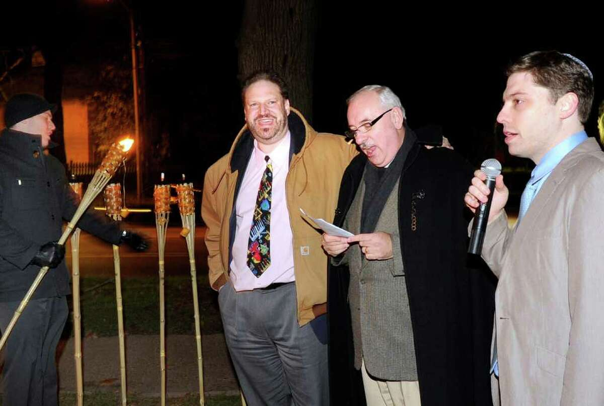 As a tiki torch menorah is lit in the background, from left, Rabbi Mitchell Hurvitz of Temple Sholom, the Rev. Dr. James Lemler of Christ Church Greenwich and Temple Sholom Cantor Asa Fradkin, lead an interfaith Celebration of Light, put on by Temple Sholom and Christ Church in front of Christ Church, Greenwich, Thursday evening, Dec. 2, 2010.