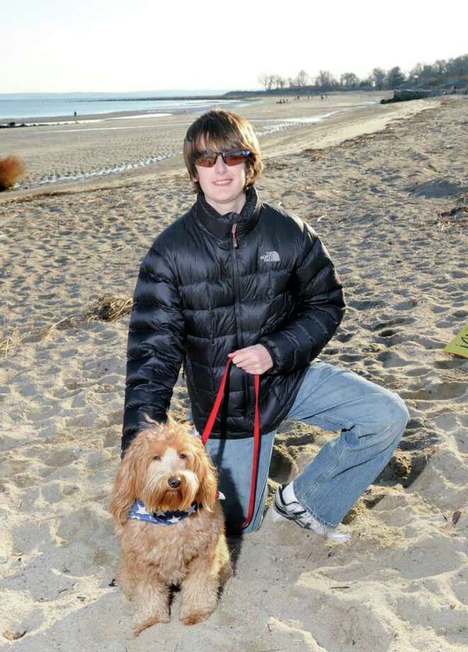 Spencer Grabel, 11, of Greenwich, poses with his miniature goldendoodle, Lucky, on the beach at Greenwich Point, Thursday, Dec. 2, 2010.  Grabel has organized a protest for 1 p.m. Saturday at Greenwich Point with hopes of changing beach access for dogs which is now limited to four months from Dec. 1 through March 31.  Grabel wants to add two extra months, November and April. Photo: Bob Luckey / Greenwich Time