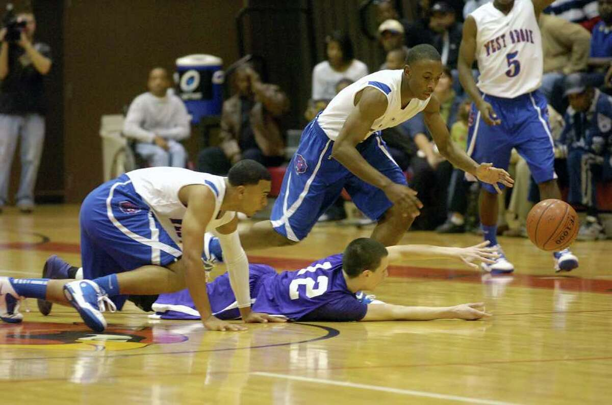 West Brook players, Derrian James, left, and Jehkenane Antoine, right, battle for a loose ball with PN-G player, Scott Pellegrin, center, during their BISD/YMBL basketball tournament game in McDonald Gym at Lamar University. December 2, 2010. Valentino Mauricio/The Enterprise