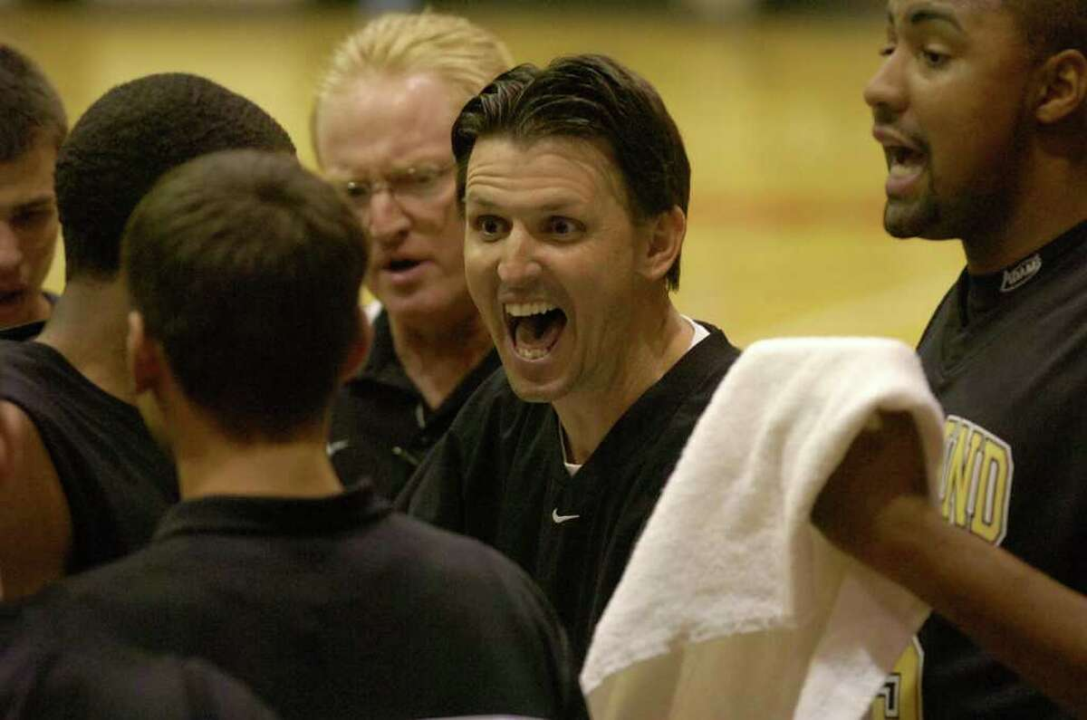 Nederland head coach Brian English, center, talks with his team during a time out against North Shore during their BISD/YMBL basketball tournament game in McDonald Gym at Lamar University. December 2, 2010. Valentino Mauricio/The Enterprise