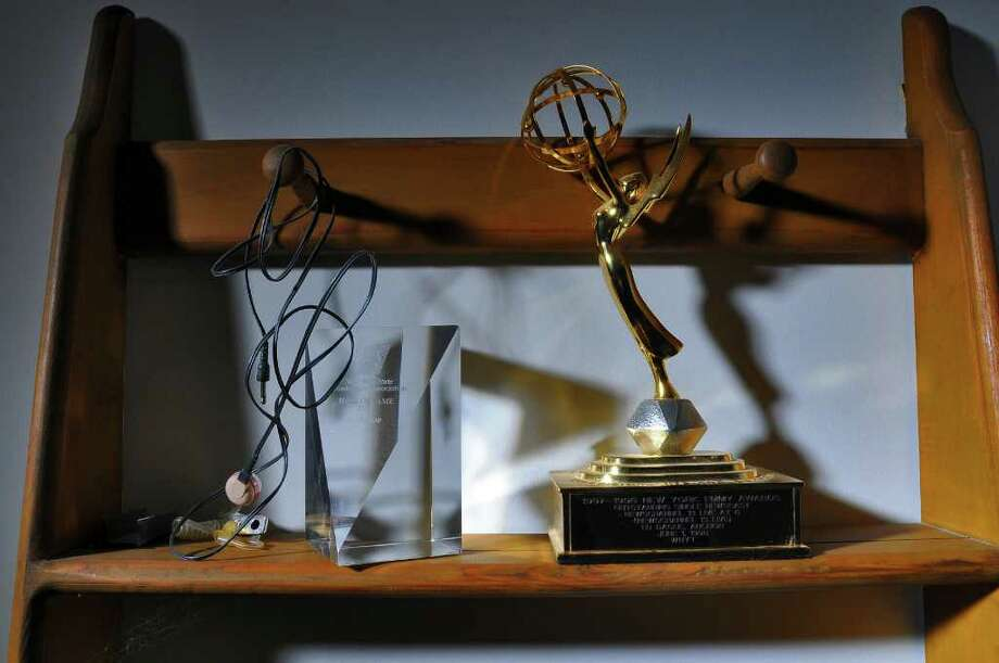 "The IFB (Internal Feedback) earpiece, left,  that retired WNYT Channel 13 anchor Ed Dague wore on the set in his last broadcast (and for many years prior to that) sits in a display next to awards he won, including an Emmy, right, in the bedroom of his Stillwater, NY home on Wednesday  December 1, 2010.  He has just published a memoir titled ""Six and Eleven,"" about his career in the news business. ( Philip Kamrass / Times Union ) Photo: Philip Kamrass"