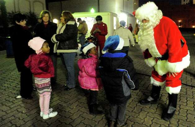 Santa Claus greets local children before the lighting of the Christmas Tree downtown in Beaumont, Thursday. Tammy McKinley/ The Enterprise Photo: TAMMY MCKINLEY / Beaumont
