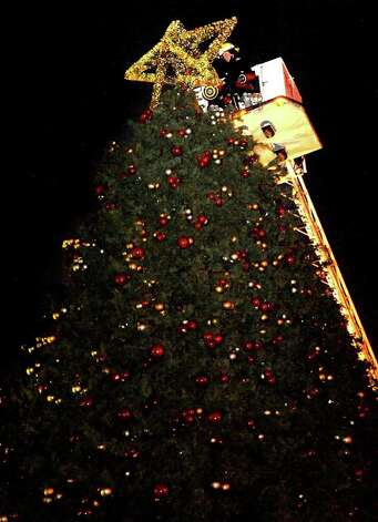 The Beaumont Fire Department places the star on top of the city Christmas Tree downtown in Beaumont, Thursday. Tammy McKinley/ The Enterprise Photo: TAMMY MCKINLEY / Beaumont