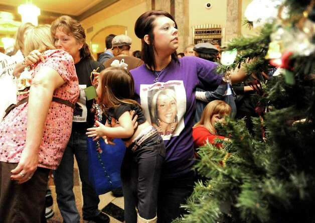 Friends and family members gather to decorate a Christmas Tree with angels during the Coalition for Victims of Crime's 9th Annual Tree of Angels Ceremony at the Jefferson County Courthouse, Tuesday. Tammy McKinley/ The Enterprise Photo: TAMMY MCKINLEY / Beaumont