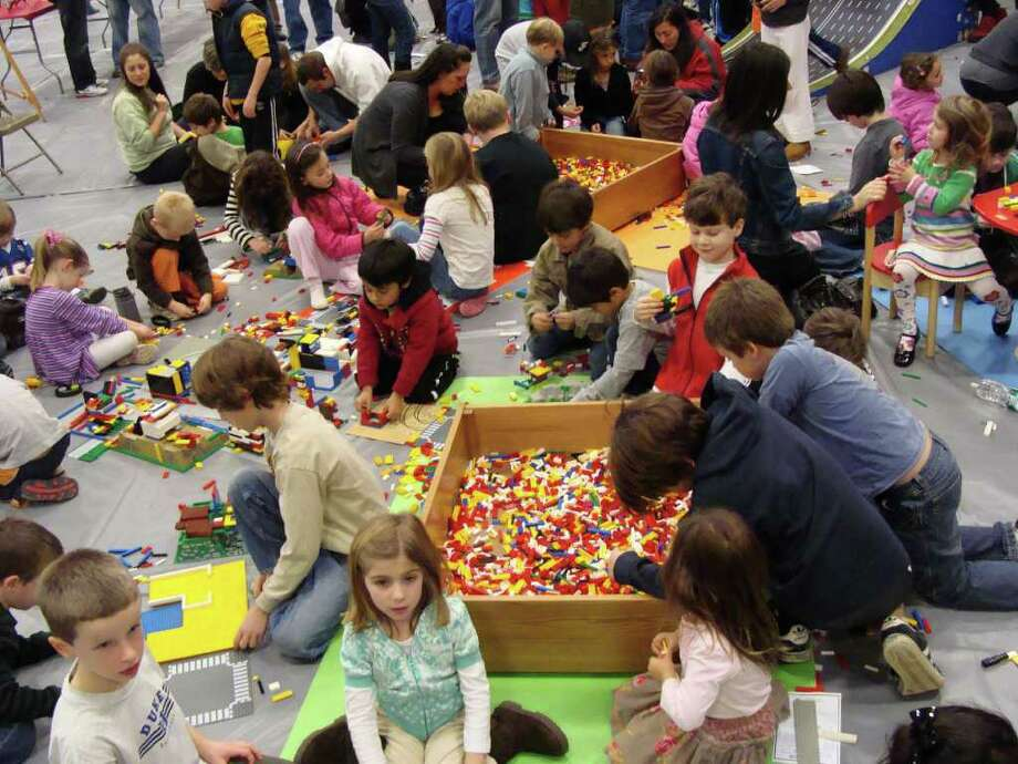 Hundreds of children and parents sat on the floor in Fairfield Ludloww High School throughout the day Saturday, Nov. 20, 2010, selecting from hundred of thousands of LEGOs in several pits to create their LEGO projects, which included structures, movie characters and vehicles that moved. Photo: Meg Barone / Westport News freelance
