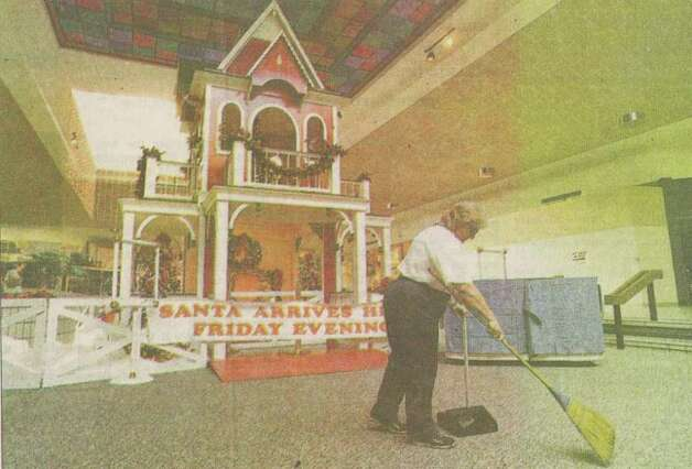 """Betty Wisecup, Parkdale Mall housekeeping employee, cleans up in front of Santa's house. Stores throughout the region are hiring additional staff to prepare for the holidays."" File photo Nov. 21, 1999"