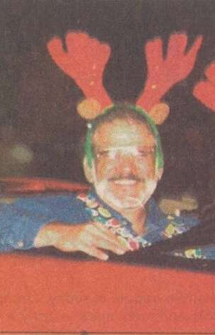 """County Judge Carl Thibodeaux, donning colorful reindeer antlers, smiles at the crowd at the 51st Annual Jaycees Christmas Parade."" File photo Dec. 8, 1999"