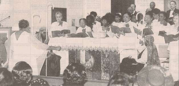 """Hazel Ruben, left, directs the choir as the shepherds kneel at the altar where the Christ child rests during the 'Prince of Peace' cantata at Our Mother of Mercy Catholic Church."" File photo Dec. 19, 1998"