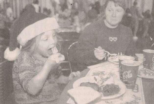"""Opal Michele Hinson, 5, tries a bite of her dinner Friday under the watchful eye of mother Michele at the City of Beaumont - H-E-B Pantry Foods 'Feast of Sharing' at the Beaumont Civic Center."" File photo Dec. 19, 1998"