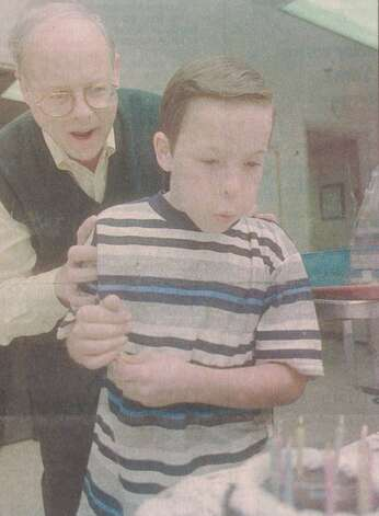 """Nickolas Page, 9, blows out candles on his birthday cake in the nursery at Beaumont M.A.S.H. with a little coaxing from pediatric surgeon Dr. Leon Hicks. Nickolas was born at the nursery on Christmas Day in 1990."" File photo Dec. 26, 1998"