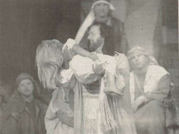 """Harold Philyaw as Jesus Christ carries Shannah Oliver, 6, down the stage Saturday night at Calvary Baptist Church after raising her from the dead during the church's holiday pageant 'Son of God, Love's Pure Light.'"" File photo Dec. 13, 1997"