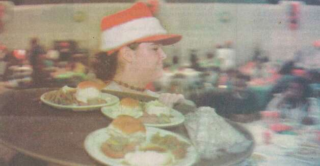 """Volunteer Michelle Bourgeois, 16, of Beaumont, carries a tray of holiday dinners Friday during the Feast of Sharing at the Beaumont Civic Center."" File photo Dec. 20, 1997"