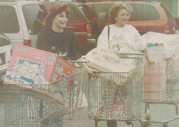 """Robin Crow and her mother-in-law Betty Crow wheel three shopping carts of Christmas gifts out of Toys R Us."" File photo Nov. 30, 1996"