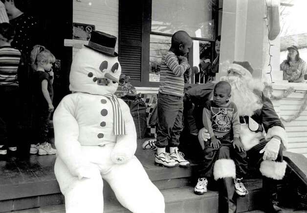 """Santa Claus and Frosty the snowman visit with children on the steps of the House of Refuge Monday after delivering gifts to the children there."" File photo Dec. 25, 1996"