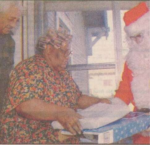 """Don Sanford helps Millie Briggs open her gift as her husband, Edward, watches from the doorway. Sanford made priority and express package deliveries while dressed as Santa Claus. He was among 23 mail carriers working on Christmas Day."" File photo Dec. 26, 1996"
