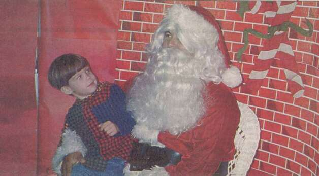 """Cory Moseley, 4, has a serious chat with Santa Claus at the Holiday Showcase at the Bridge City High School cafeteria."" File photo Nov. 29, 1995"