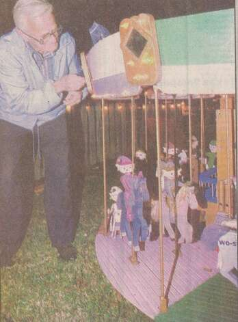 """Liles Wolfford works at Tex Ritter Park in Nederland to put up the carousel of the miniature carnival he and his wife built. The Wolffords have been putting up the display each year for the past five."" File photo Dec. 10, 1995"