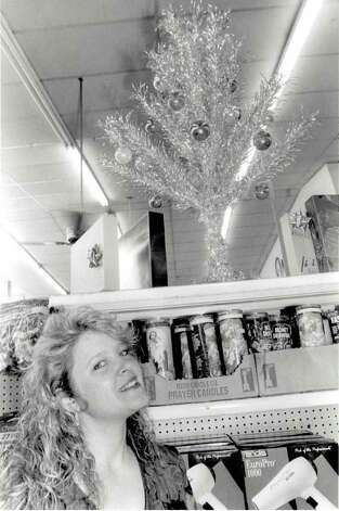 """Debbie Wehmeyer, office manager at Willee's Grocery Store in Port Arthur, with the alumnium Christmas tree in the store."" File photo Dec. 14, 1995"