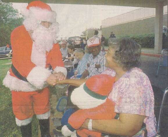 """Jerry Wheat of Beaumont, an inmate in the Positive Production program at the Jefferson County jail, poses recently as Santa Claus as he greets Jessie Cunningham, 75, a resident at the Schlesinger Geriatric Center."" File photo Dec. 19, 1995"