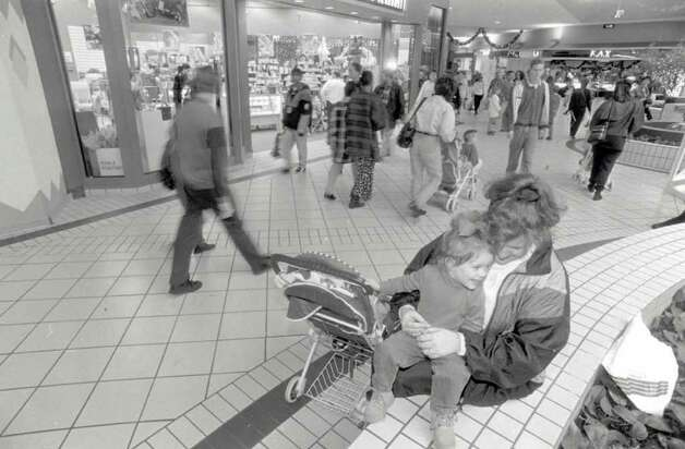 """Gena Campbell and her daughter, Carson, 2 take a break from shopping Wednesday at Parkdale Mall. Retailers have reported an increase in shoppers."" File photo Dec. 21, 1995"
