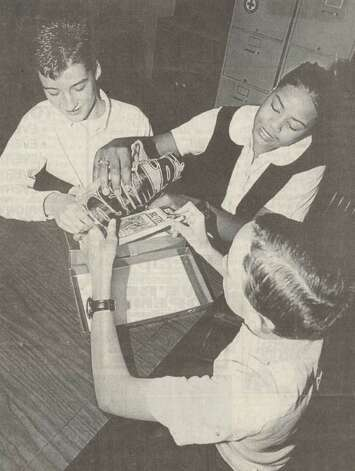 """Beaumont's Cathedral Christian School seventh graders Justin Jones, Christian Watson and Joseph Markham fill a shoe box with items to send to children in Bosnia or Rwanda through Operation Christmas Child, which is an international project of Samaritan's Purse."" File photo Dec. 23, 1995"