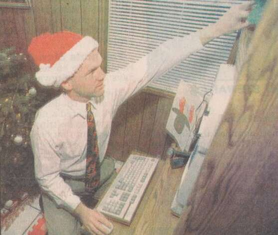 """Joseph 'Sparky' Nolan, a Beaumont man who has set up a computer voicemail line to Santa's Wokshop, adjusts the volume on an incoming call at his computer workstation."" File photo Dec. 23, 1995"