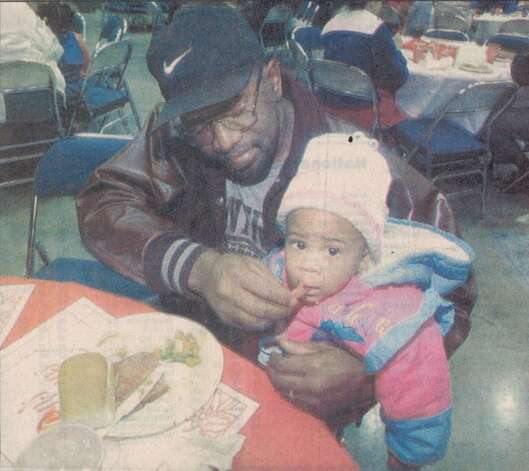 """Elton Redeaux of Beaumont feeds a piece of ham to his 2-year-old granddaughter, Santana Sorrell, at the 'Feast of Sharing' Friday at the Beaumont Civic Center."" File photo Dec. 23, 1995"