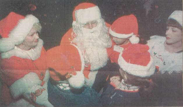 """Jared Munoz sits on Santa's lap while he and his foster sisters talk with Santa at the party for Jefferson County foster children."" File photo Dec. 25, 1995"
