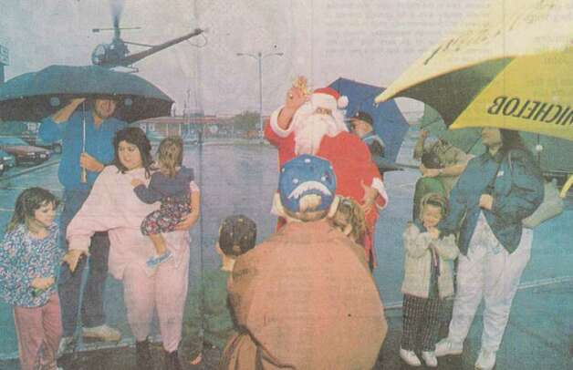 """Santa Claus arrived at Gateway Friday morning by helicopter despite the rain. Parents held umbrellas and coats over their kids to keep them dry while they waited."" File photo Nov. 26, 1994"