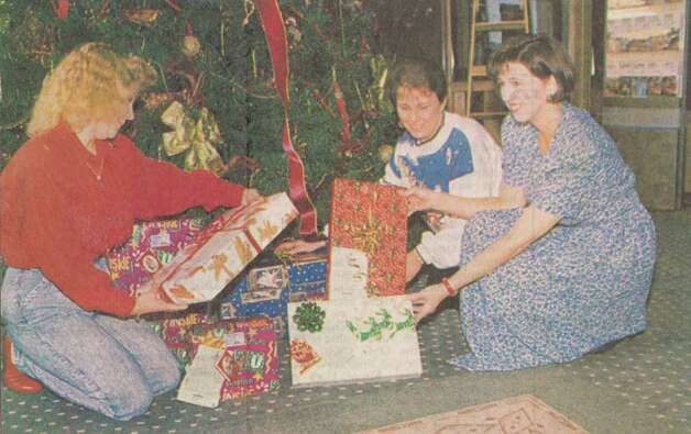 """Dianne Stephenson, left, Sandy Meche and Ida Schossow sort gifts for needy children."" File photo Dec. 14, 1994"